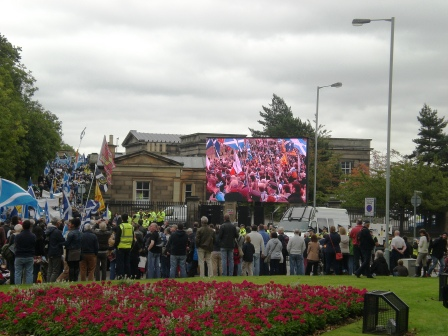 The March heads up the entrance to Calton Hill. A big screen had been displayed at the park entrance. Pic copyright Alistair McConnachie