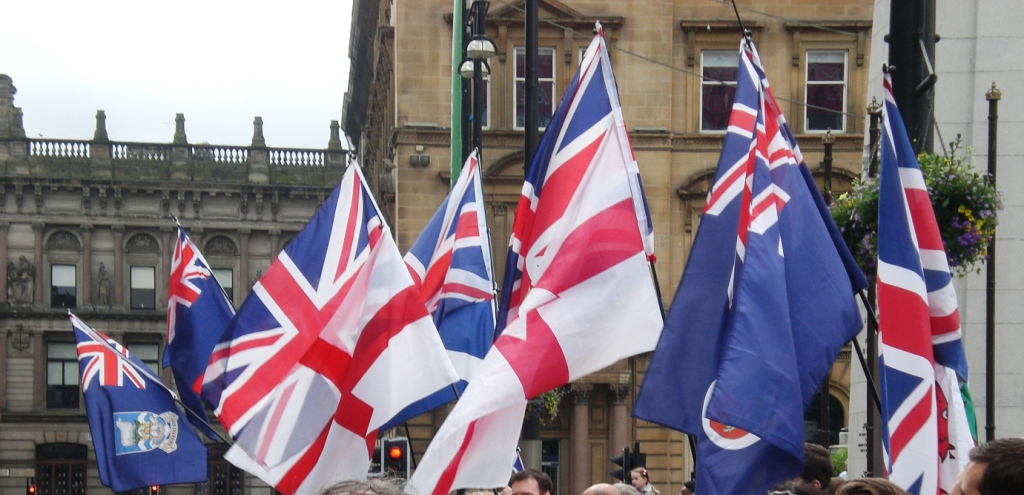 The Union Jack, flags of all the Home Nations, and flags of some of the British Overseas Territories greet the arrival of the Queen's Baton Relay, and its Baton Bearers, outside Glasgow City Chambers on Sunday 20th July 2014.